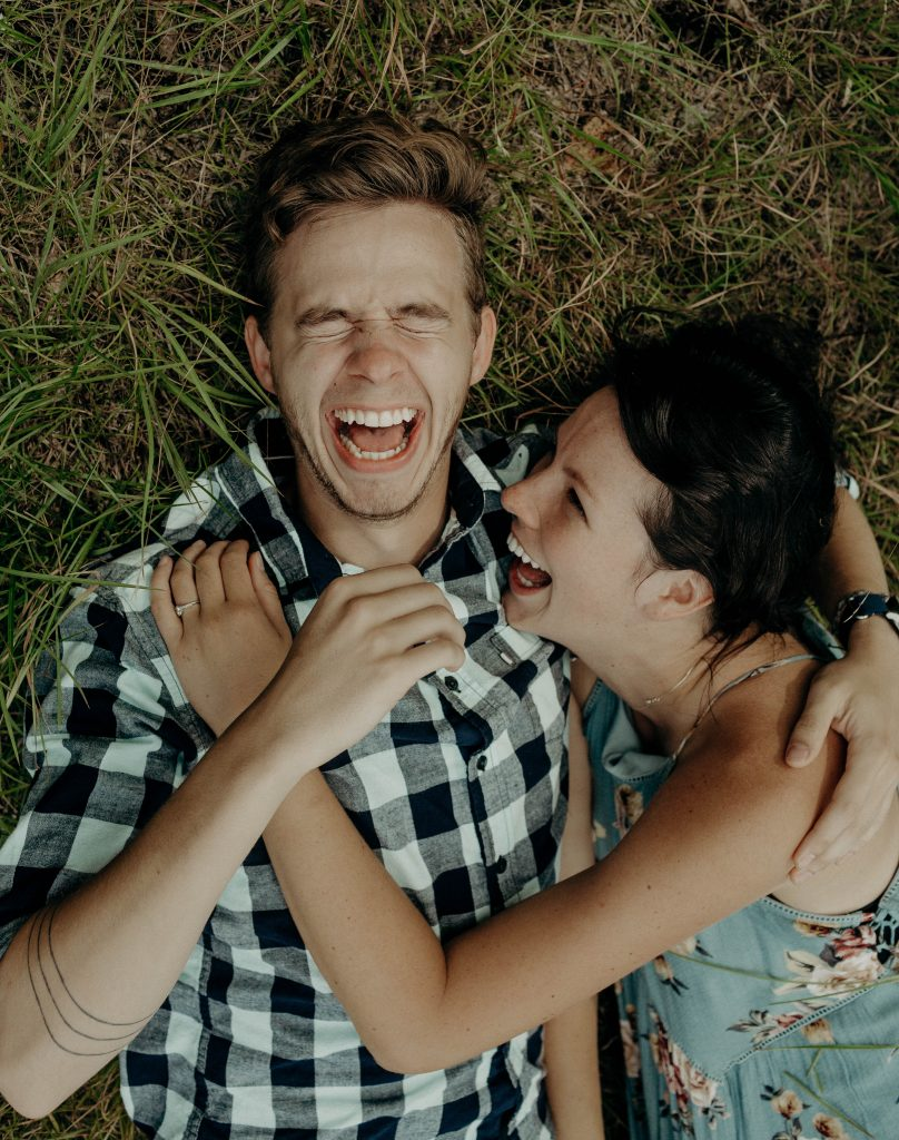 couple laughing while laying down in grass